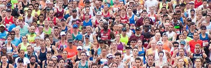 Groups of runners crossing the start line of the Bank of America Chicago Marathon